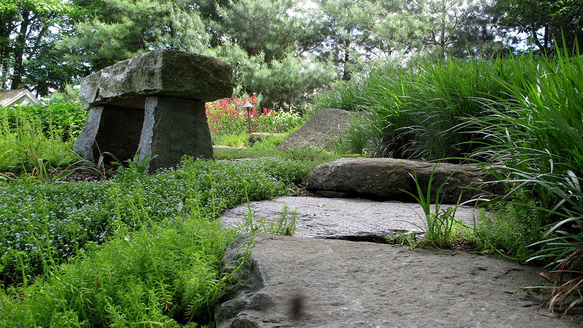 A Salvaged Granite Bench Provides a Seating Area to View the Pond
